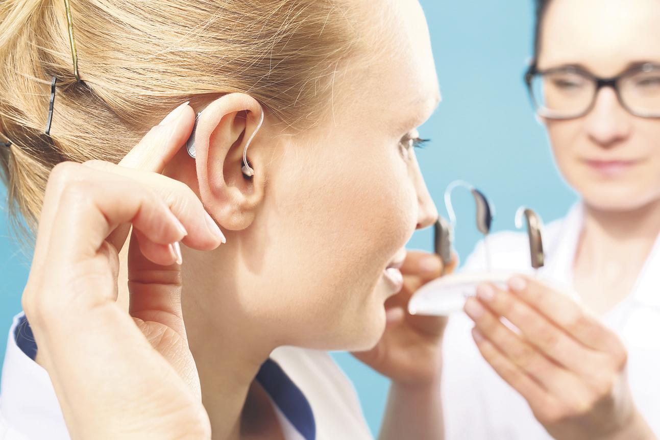 Frau bei der Anpassung eines modernen Hörgerätes.