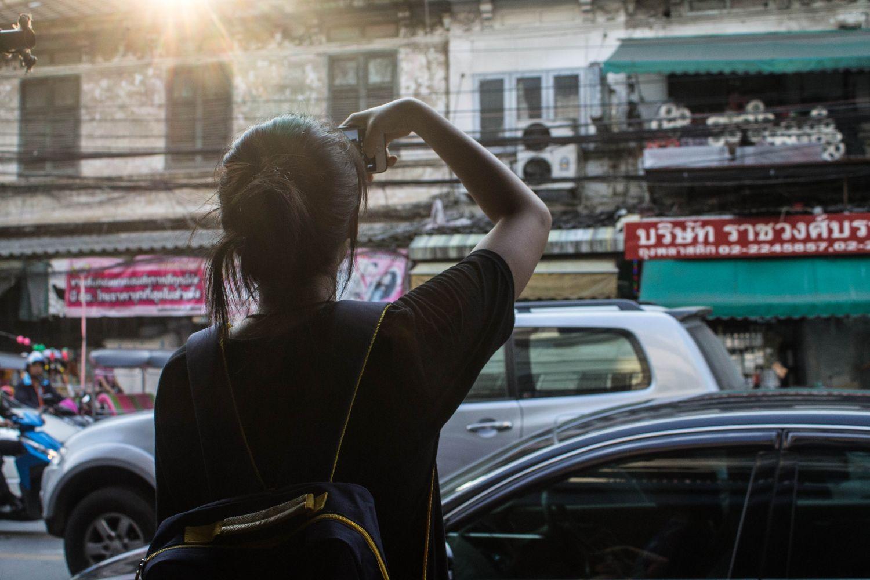 Eine Frau steht an einer viel befahrenen Straße und fotografiert etwas. Thema: Gehörschaden