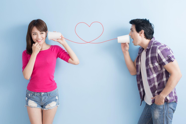 Eine Frau und ein Mann kommunizieren über ein Dosentelefon. Barrierefreie Telefone funktionieren anders.
