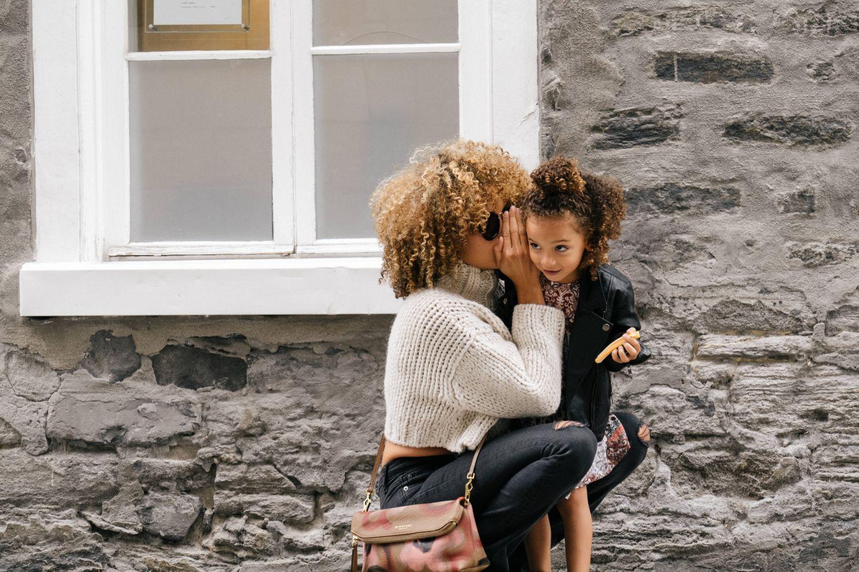 Mutter flüstert ihrem Kind etwas ins Ohr. Thema: Eingeschränktes Hörvermögen