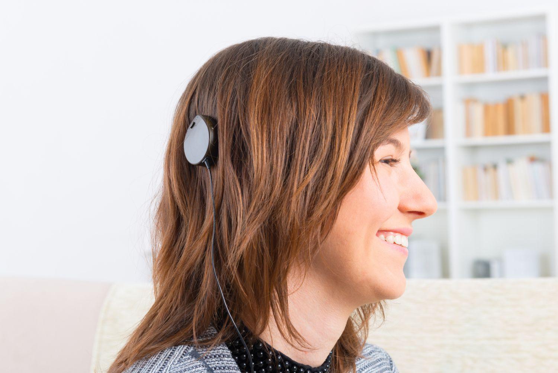 Eine Frau mit einem Cochlea-Implantat lächelt. Thema: Hörimplantate