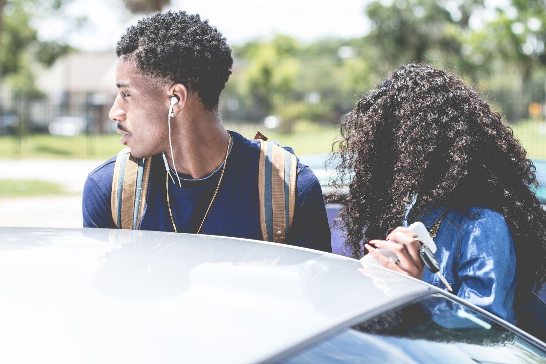 Zwei junge Menschen mit Kopfhörern stehen vor einem Auto. Thema: Hörschäden durch Kopfhörer