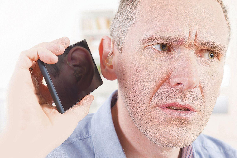 Ein Mann hält sein Smartphone ans Ohr. Thema: Hilfsmittel für Hörgeschädigte