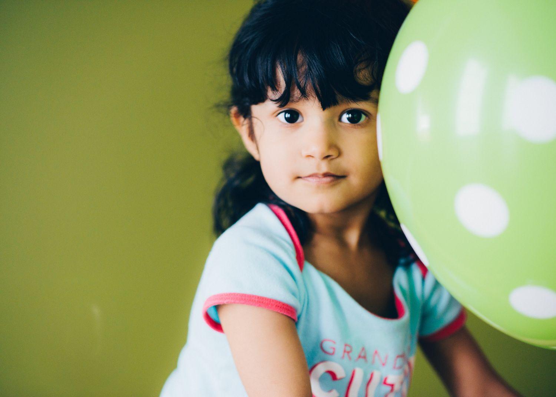 Kleines Mädchen spielt mit Luftballon. Thema: Grauer Star bei Kindern