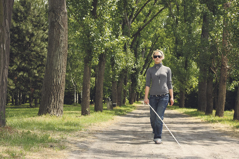 Blinde Frau geht spazieren mit einem Blindenstock in ihrer Hand.