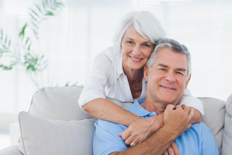 Eine alte Frau umarmt einen alten Mann. Dank digitaler Hörsysteme wird Fernsehen für Menschen mit Hörproblemen wieder zum Erlebnis.