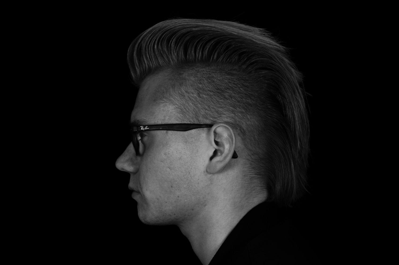 Schwarz-weiß-Profilansicht eines Mannes mit Irokesenschnitt und Brille. Thema: Glaukomvorsorge