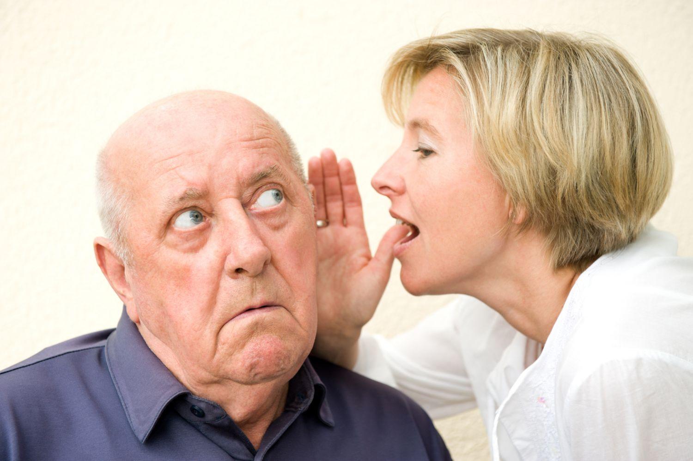 Eine Frau sagt einem älteren Mann etwas ins Ohr.