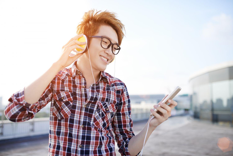 Eine Person hört über Smartphone und Kopfhörer Musik.