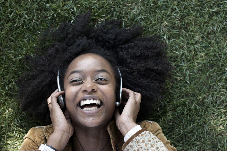Eine Frau liegt mit Kopfhörern im Gras und freut sich. Thema: Hilfsmittel bei Seh- oder Hörschwäche