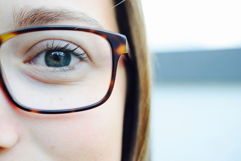 Halbes Gesicht einer jungen Frau mit Brille – mit Fokus auf dem Auge. Thema: Erbliche Augenerkrankungen