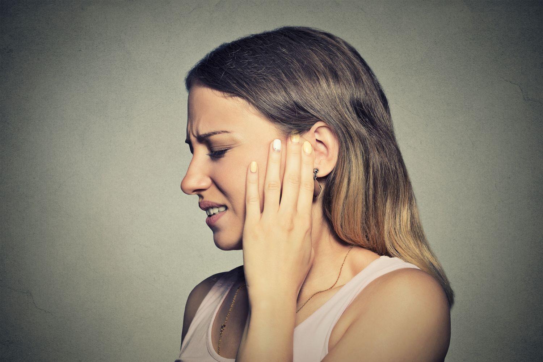 Eine Frau mit schmerzverzerrtem Gesicht hält die Hand vors Ohr